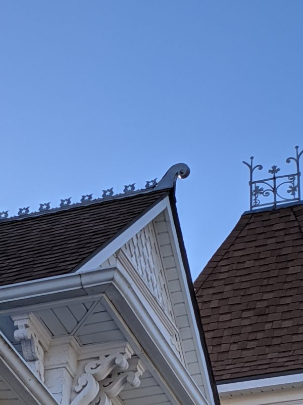 Cutout rounded shapes line the top of the gabled roof.
