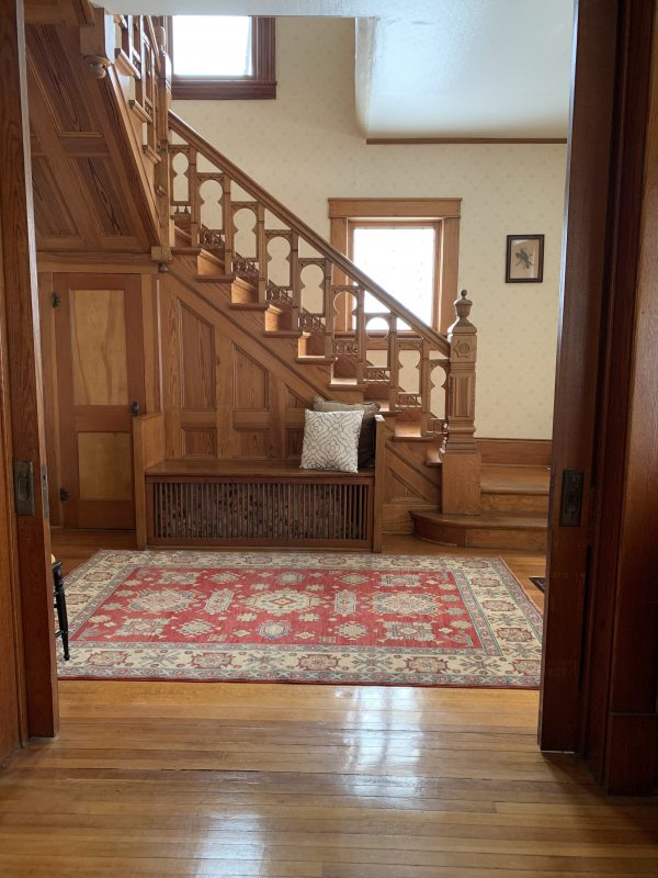 A oak staircase to the second floor, a red and tan patterned rug and shiny hardwood floors are shown in the Victorian-style house.