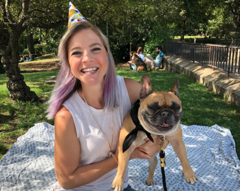 Chelsea Amengual smiles and wears a party hat while sitting outside on a blanket and holding her French bulldog.