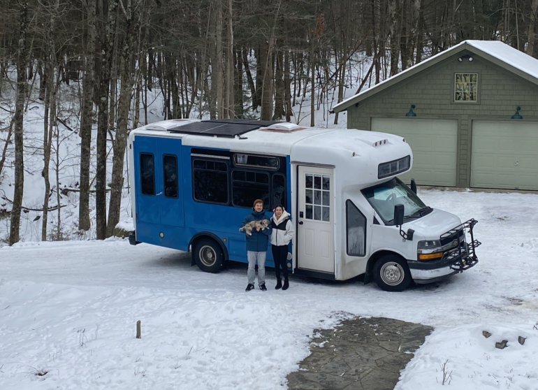 Dan Howson and Bo Bean stand outside their bus with their dog, Taro. The couple converted the bus into a living space in 2020.
