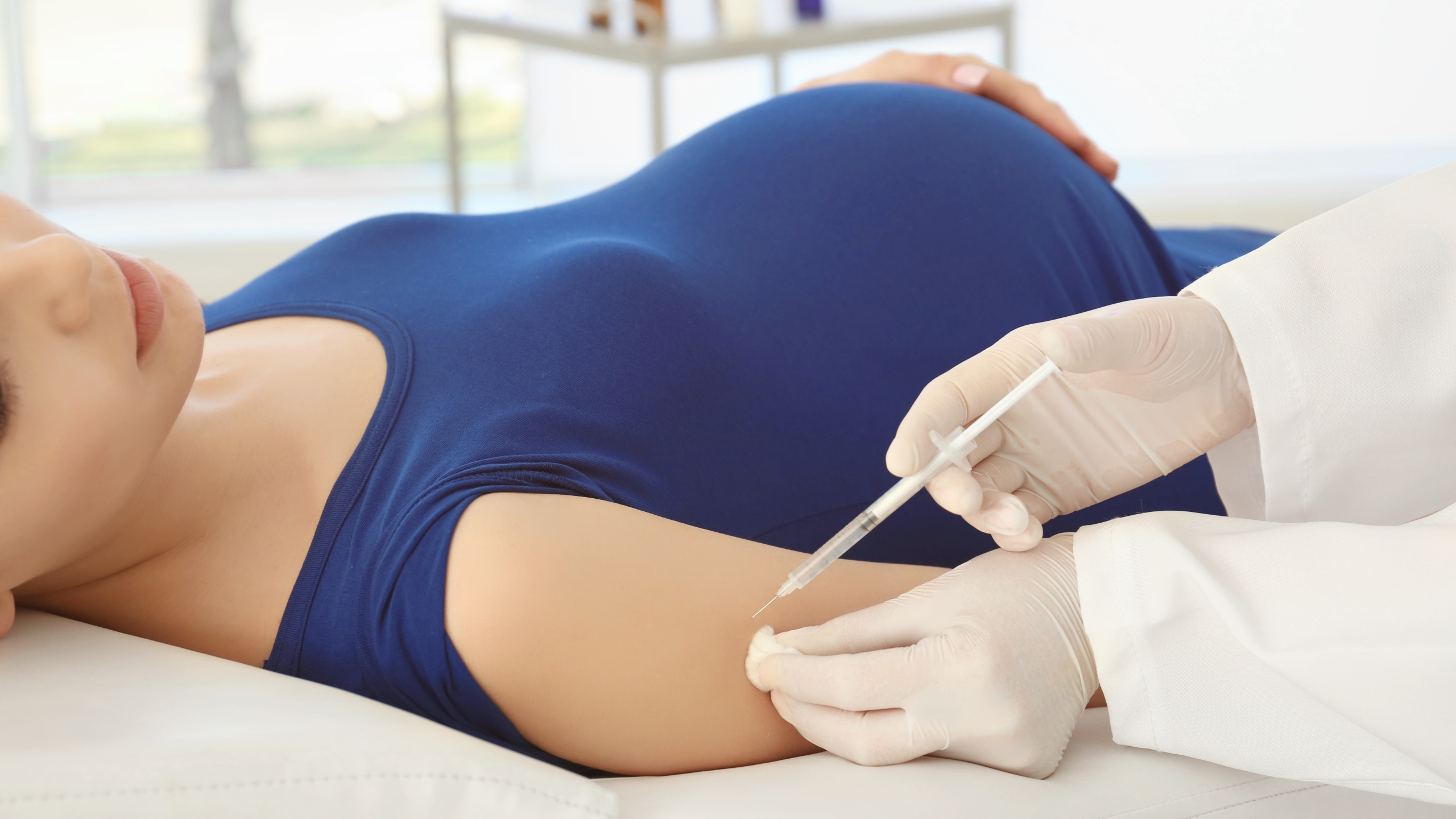 Young pregnant woman receiving vaccination in clinic