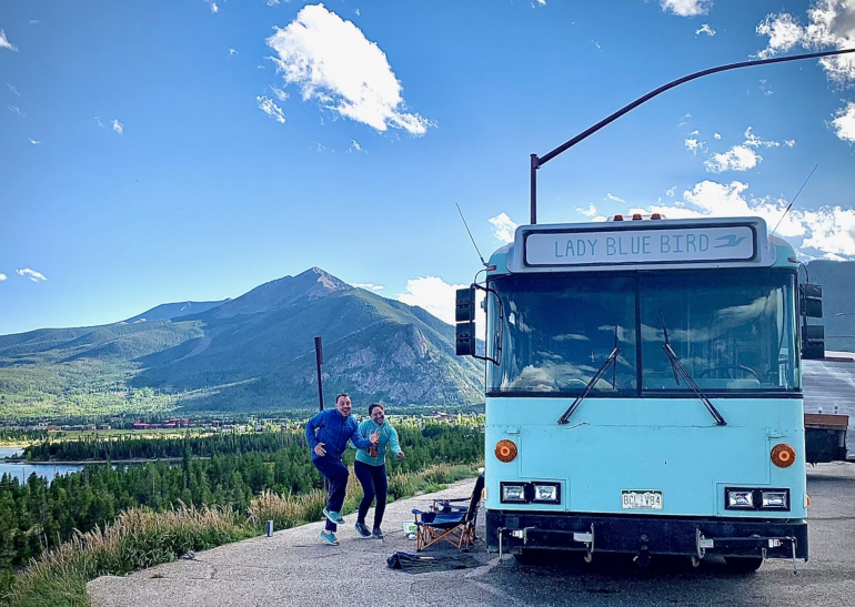 Steve and Carly Schneiter make running motions outside their blue bus that's parked near a lake.